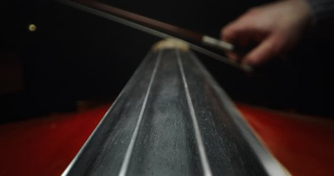 Slow motion artistic macro of master artisan luthier playing with a bow on a handmade violin or cello. Shot in 8K. Concept of spiritual instrument, art, orchestra, passion for music, sound, precision