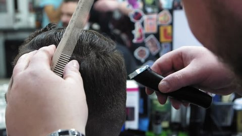 Men's hairstyling and haircutting in a barber shop or hair salon. Grooming the hair. Barbershop. Men hairdresser doing haircut adult men in the men's hair salon. Haircutter in the workplace. 4k