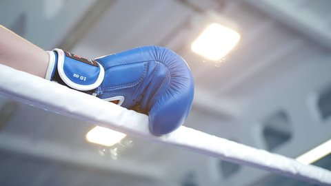 Boxer leaned on the ropes of the ring blue Boxing glove close-up.