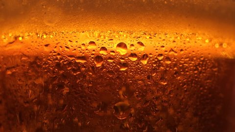 Extreme close-up transparent glass full of fresh craft beer with rising up air bubbles slowmo. Macro shot cooled alcohol golden beverage with foam in bocal with water drops