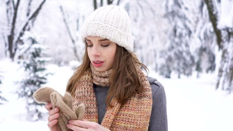 84544ef544f Pretty young woman in in winter city park put on mittens and smile in