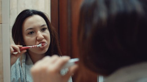 Brunette girl brushes her teeth. Reflected in the mirror. Morning treatments.