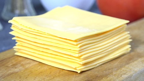 Closeup of pulling slices of processed cheese off a stack