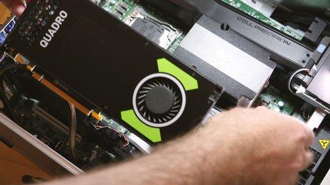 Paris, France - Feb 20, 2019: IT professional removing Nvidia Quadro P4000 workstation professional video card GPU for professional in dual CPU Dell Precision T7910 workstation