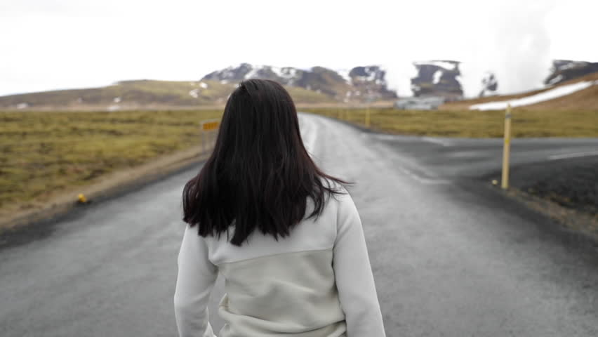 Girl Walking Down Road in Iceland with Steam Clouds in Background in Slow Motion.