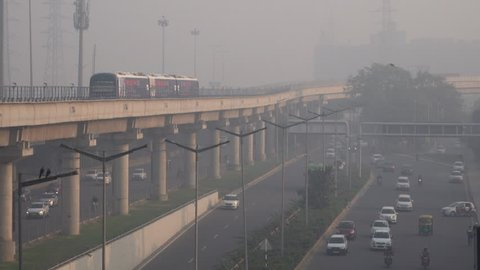 CYBER CITY, GURUGRAM, INDIA - NOV 24: Metro train and traffic in hazardous levels of air pollution on November 24, 2018 in Cyber City, Gurugram, India