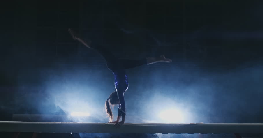 The girl is a professional athlete performs gymnastic acrobatic trick on a beam in backlight and slow motion in sports gymnastic clothing. Smoke and blue. Jump and spin on the balance beam | Shutterstock HD Video #1024774247