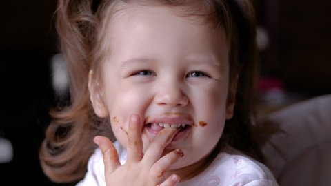 Closeup view of funny dirty small girl after eating chocolate. Brown lips and teeth. Child licking fingers.