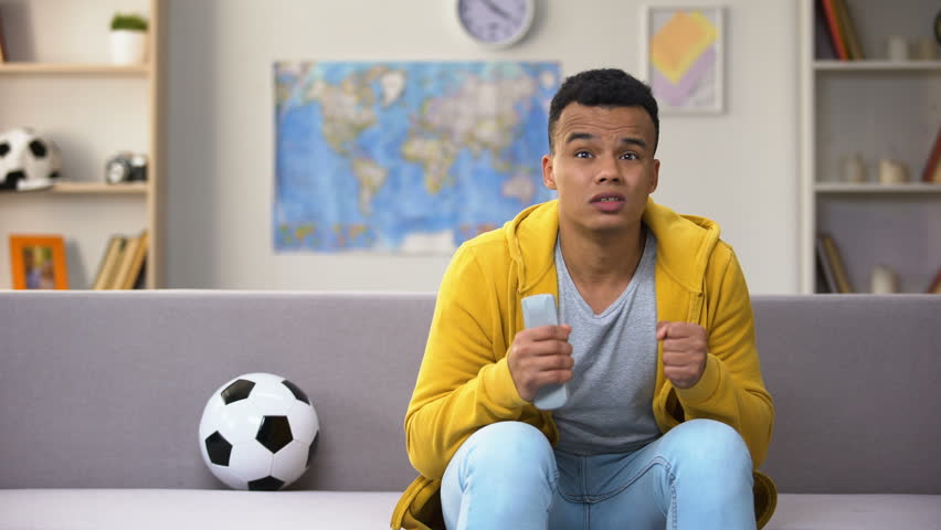Disappointed black teenager watching football match on TV upset with team losing | Shutterstock HD Video #1024828817