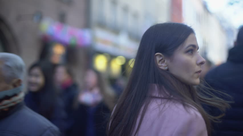 Nervous young female criminal walking on crowded street and turning around | Shutterstock HD Video #1024829627
