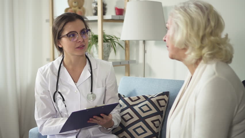 Smart specialist listen happy and smiling aged lady, holding form for notes and writing down prescription for patient. Doctor making recommendation to symptom or problem | Shutterstock HD Video #1024834847