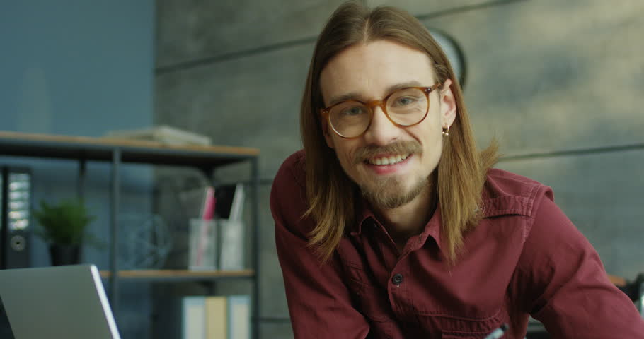 Portrait shot of the young cheerful Caucasian man in glasses and with long hair smiling sincerely to the camera in the office with laptop computer on the table. | Shutterstock HD Video #1024840457