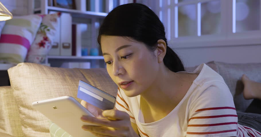 Attractive young asian woman using digital pad while relaxing on sofa at home shopping online holding credit card doing payment on bargain price product. rich lady buying new cloth on sale