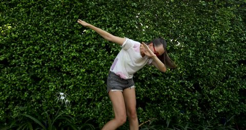Slim woman in shorts and t-shirt performing dab dance movement standing against green bushes on street