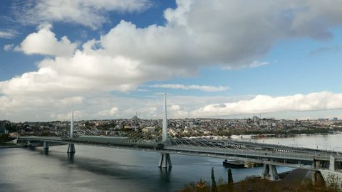 White cumulus clouds fly fast over Golden Horn and Halic Metro Bridge, Old Istanbul area, Fatih district on background. Panoramic time lapse shot from height, lively car traffic on Ataturk bridge