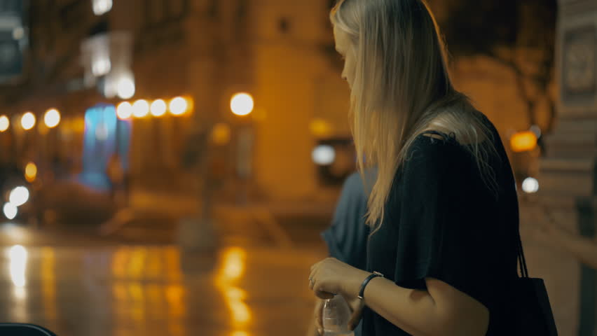 Young blond woman standing in the street of night city and drinking water from plastic bottle | Shutterstock HD Video #1024882967