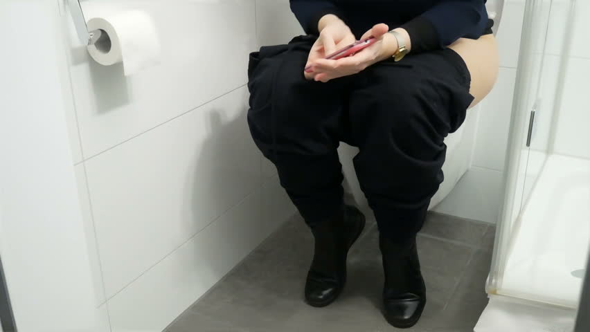Woman sitting on toilet stock photo. Image of feet