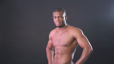 Attractive African male fighter or boxer posing shirtless, isolated over dark background. Muscular fitness man under dramatic low key lighting.