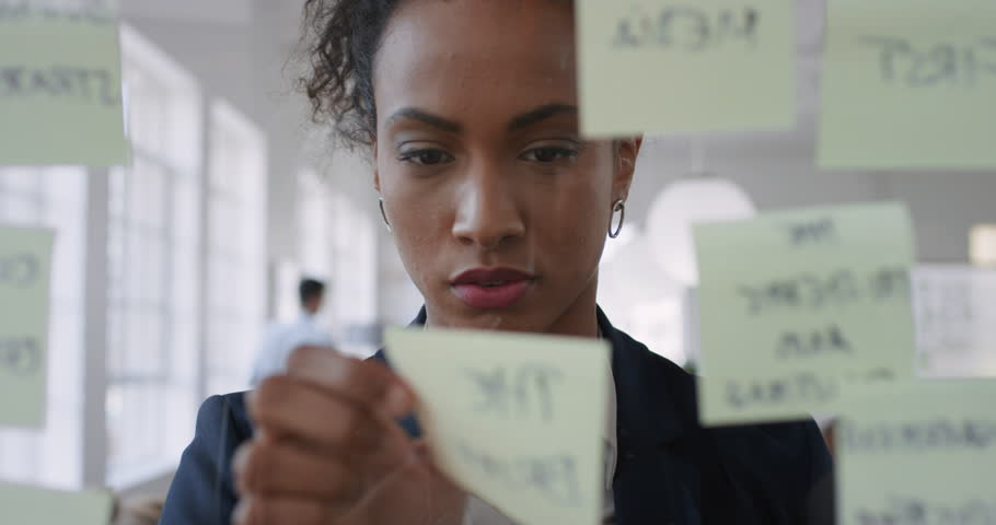 Mixed race business woman using sticky notes brainstorming ideas problem solving with creative mind map planning strategy in office working on solution