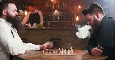 Two bearded friends drinking and smoking while playing chess in a pub. A man inhales the smoke from his electronic cigarette and another man drinks bourbon