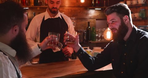 Men clinking glasses of whiskey at a bar counter. Two good friends drinking whiskey at a bar counter. Bartender is cleaning the glass.