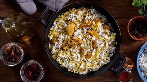 Biryani with chicken. Traditional Indian dish of rice and chicken marinated in spices and yoghurt.Sprinkling with fried onions. Slow motion.