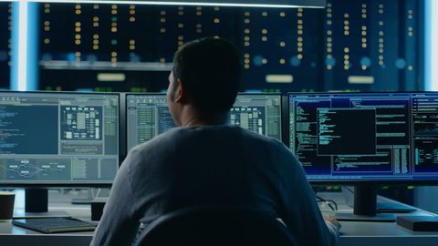 IT Specialist Takes His Place at the Desk and Starts Working on Personal Computer with Screens Showing Software Program with Coding Language Interface. In the Background Technical Room of Data Center.