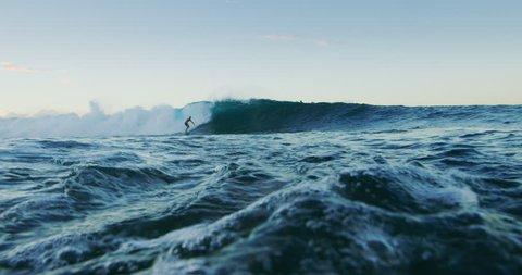 Surfer carves epic turn on wave at sunset, summer adventure lifestyle