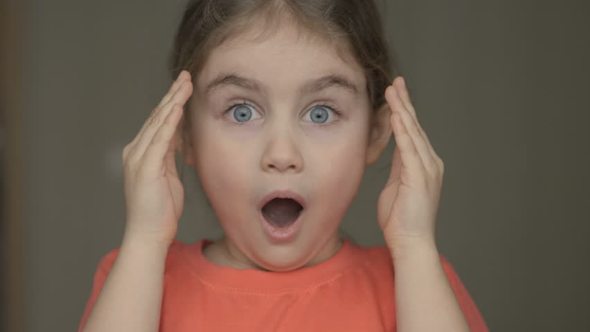 Cute little girl open her face with hands. Girl looks and is surprised and happy to receive a surprise. Portrait little young girl with blue eyes looking at camera. Closeup | Shutterstock HD Video #1025114267