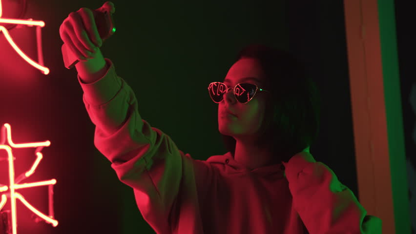 Female cute teen in sunglasses taking selfie using smartfone. Red illumination. Attractive brunette girl looks at herself with mobile device and adjusting her dark short hair. | Shutterstock HD Video #1025122397