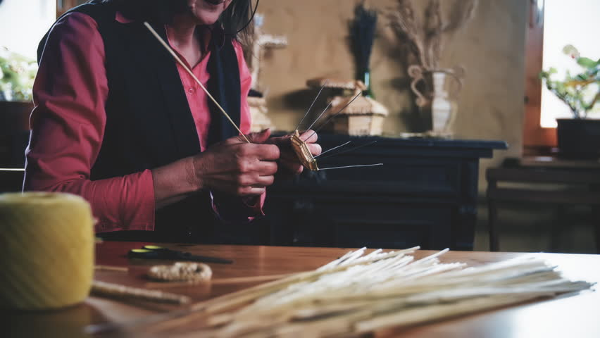 Knitting with straws. Medium slow motion shot of a headless woman in focus making a product from dried straws. | Shutterstock HD Video #1025143757