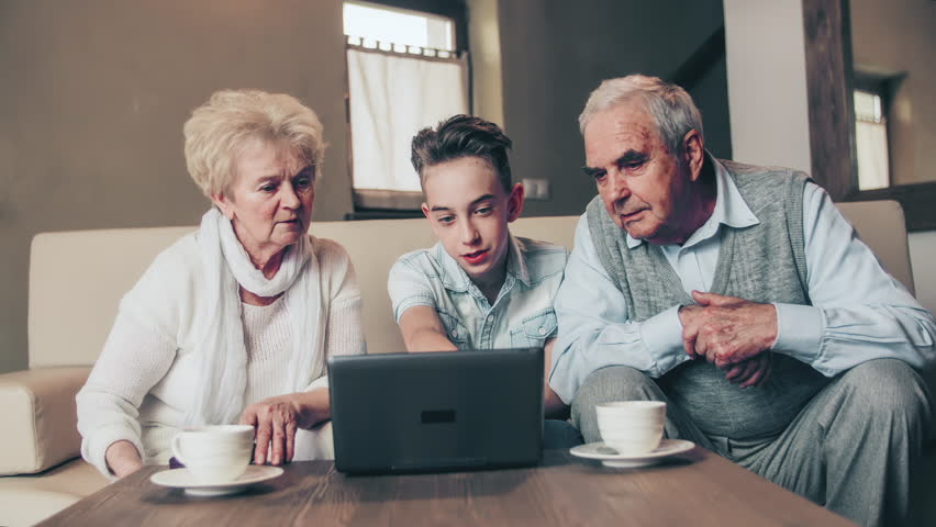 Grandparents with grandson looking at computer. Medium shot of three people in focus sitting on a couch in the living room looking at a laptop computer on the tea table. | Shutterstock HD Video #1025143787