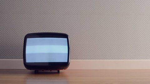 Vintage old television on the floor with static screen, retro wallpaper on background
