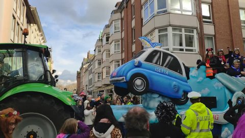 Dusseldorf, Germany - March 3, 2019. Traditional street carnival. Unidentified people cheering carnival floats and traditional groups at the street parade. Float with a BMW Isetta