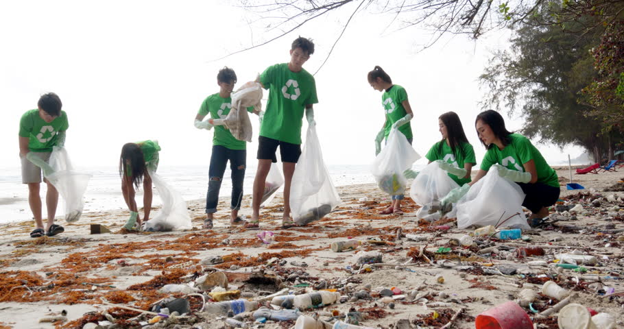 Group of asian people cleaning up the beach with plastic bags full of garbage. People with environment and volunteering concept. 4k resolution. | Shutterstock HD Video #1025209217