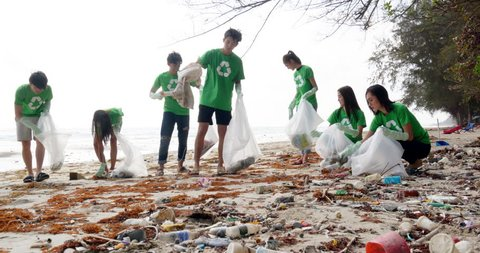 Group of asian people cleaning up the beach with plastic bags full of garbage. People with environment and volunteering concept. 4k resolution.