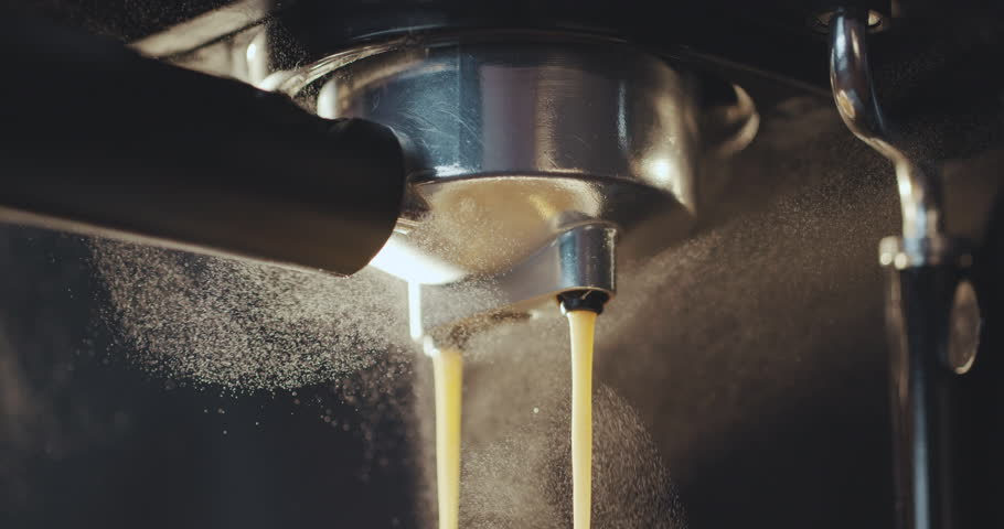 Pouring coffee stream from professional machine in cup. Barista man making double espresso, using filter holder. Flowing fresh ground coffee. Drinking roasted black coffee in the morning #1025245037
