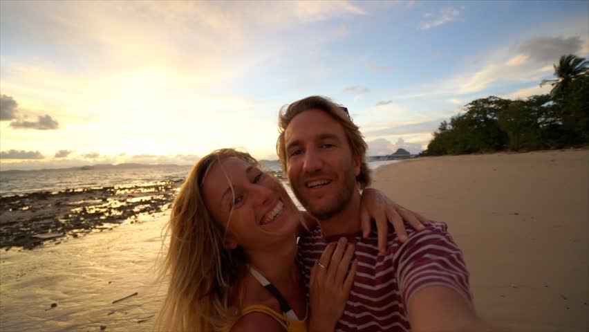 Couple on vacation taking selfie on the beach at sunset. Young couple selfies point of view  | Shutterstock HD Video #1025256077