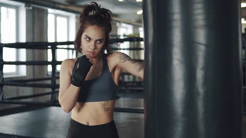 closeup portrait of a boxer girl. attractive kickboxing woman training punching bag in fitness studio