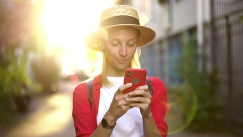 Soft focus on phone.Slow motion of positive smiling hipster girl holding smartphone and browsing social network on web page.Female travel blogger posting new publication during summer vacations abroad