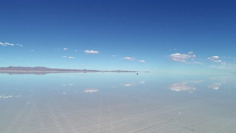 Aerial view of world's largest salt flat Salar de Uyuni, sky reflection on water surface - landscape panorama of Bolivia from above, South America