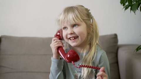 A little blonde girl in a gray t-shirt sits on a laconic gray sofa in a modern apartment, holds a stylish stained-glass red phone in her hands and talks to her girlfriend
