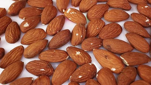 Whole almond almonds nut nuts closeup texture video on rolling rotating looping plate