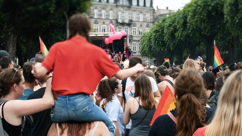 STRASBOURG, FRANCE - CIRCA 2018: Tilt-shift lens over large crowd of people waving rainbow flags at annual FestiGays pride gays and lesbians parade marching street with gay truck in front