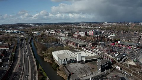 Aerial footage of trains approaching Stoke on Trent train station in the midlands by the canal, waterside and A50 motorway, the midway point for commuters who travel north and south through the UK