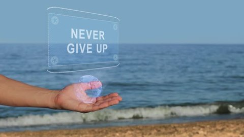 Male hands on the beach hold a conceptual hologram with the text Never give up. A man with a holographic technology on the background of the sea