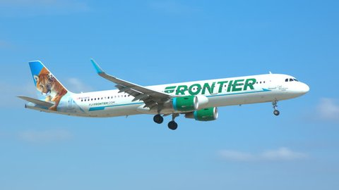MIAMI, FL - 2019: Frontier Airlines Airbus A321 Commercial Jet Airliner featuring Cali the Mountain Lion Landing at MIA Miami International Airport on a Sunny Day in South Florida