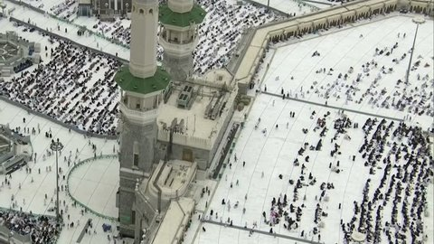 MECCA, SAUDI ARABIA - March 2019: Crowd of people walking around Masjid Al Haram in Mecca. Aerial skyline view from Abraj al Bait tower. During Umrah or Hajj.