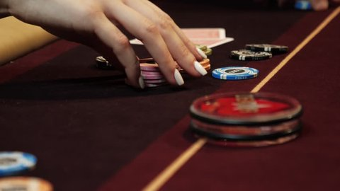 Playing poker. Woman is nervous, fingering the chips in her hand on the poker table. Hand close up. Casino gamble.