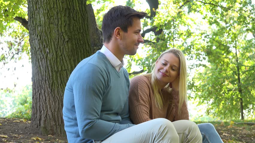 A man and a woman (both young and attractive) sit in a park on a sunny day and dance #1025532827